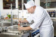 Cocinero que usa el cepillo para preparar un plato en la cocina Imágenes de archivo libres de regalías