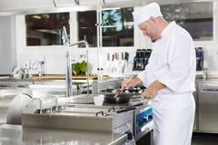 Cocinero que usa el cepillo para preparar un plato en la cocina Imagenes de archivo