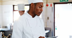 Cocinero que usa la tableta digital en cocina almacen de metraje de vídeo