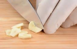 Cocinero Slicing Garlic Fotos de archivo libres de regalías