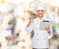 Cocinero sonriente con la PC de la tableta que muestra los pulgares para arriba Foto de archivo libre de regalías