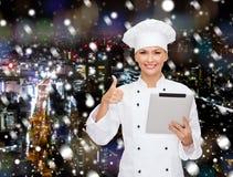 Cocinero sonriente con la PC de la tableta que muestra los pulgares para arriba Foto de archivo