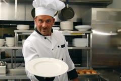 Cocinero sonriente con la placa vacía foto de archivo