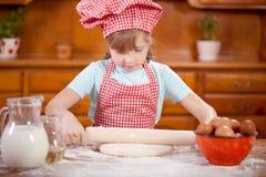 Cocinero sonriente feliz de la chica joven en la cocina que hace la pasta Fotos de archivo libres de regalías