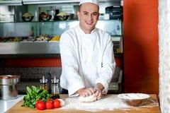 Cocinero sonriente que prepara la base de la pizza fotos de archivo libres de regalías