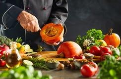 Cocinero vegetariano que quita pipas de una calabaza imagen de archivo libre de regalías