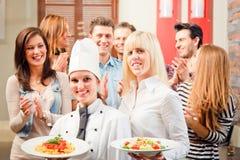 Cocinero And Waiter With sus huéspedes Fotos de archivo