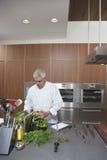 Cocinero Washing Leafy Vegetables en cocina comercial imagen de archivo libre de regalías