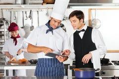 Camarero y cocinero que usa la tableta de Digitaces en cocina Foto de archivo