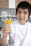 Cocinero y un vidrio del huevo sin procesar Foto de archivo