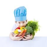 Cocinero y verdura del muchacho aislados en blanco Fotografía de archivo