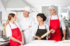 Cocineros alegres que conversan en cocina comercial Imágenes de archivo libres de regalías