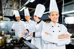Cocineros asiáticos en cocina del restaurante del hotel imágenes de archivo libres de regalías