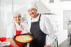 Cocineros confiados con la pizza Pan At Commercial Imagenes de archivo