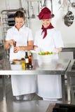 Cocineros de sexo femenino que preparan la comida en cocina Fotografía de archivo