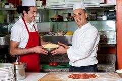 Cocineros de sexo masculino en cocina en el trabajo Foto de archivo libre de regalías