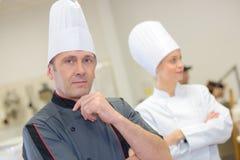 Cocineros de sexo masculino y de sexo femenino en uniforme foto de archivo