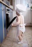 Cocineros del cocinero del bebé en la comida del horno Fotos de archivo libres de regalías