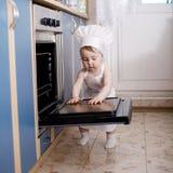 Cocineros del cocinero del bebé en la comida del horno Foto de archivo libre de regalías