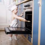 Cocineros del cocinero del bebé en la comida del horno Imagen de archivo