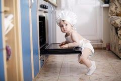 Cocineros del cocinero del bebé en la comida del horno Imágenes de archivo libres de regalías