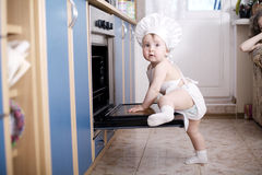 Cocineros del cocinero del bebé en la comida del horno Fotos de archivo