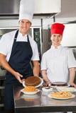 Cocineros felices con la variedad de platos dulces Foto de archivo libre de regalías