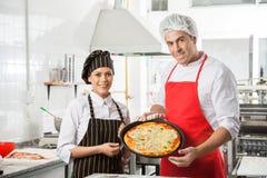 Cocineros felices que presentan la pizza en la cocina comercial Fotografía de archivo libre de regalías