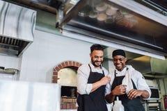 Cocineros profesionales sonrientes que trabajan en cocina del restaurante foto de archivo libre de regalías