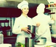 Cocineros que cocinan en la cocina profesional imagen de archivo libre de regalías