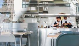 Cocineros que cocinan la comida junta en la cocina del restaurante imagenes de archivo