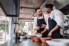 Cocineros que hablan mientras que cocina la comida en cocina comercial imágenes de archivo libres de regalías