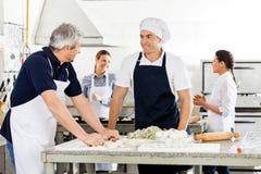 Cocineros que hablan mientras que prepara las pastas en el anuncio publicitario Fotos de archivo libres de regalías