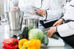 Cocineros que preparan comidas en cocina comercial Imagen de archivo libre de regalías