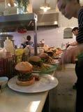 Cocineros que preparan las hamburguesas en una cocina del restaurante Imágenes de archivo libres de regalías