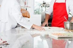 Cocineros que preparan las pastas de los raviolis en el contador Foto de archivo libre de regalías