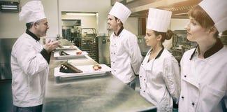 Cocineros que presentan sus placas de postre al chef en cocina fotografía de archivo