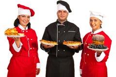 Cocineros que sirven la comida Foto de archivo libre de regalías