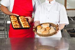 Cocineros que sostienen los panes cocidos en cocina Imagenes de archivo