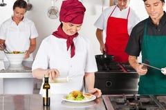 Cocineros que trabajan en cocina Imagenes de archivo