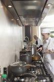 Cocineros que trabajan en cocina comercial Imágenes de archivo libres de regalías