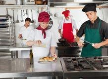 Cocineros que trabajan en cocina del restaurante Imágenes de archivo libres de regalías