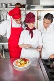 Cocineros que usan la tableta de Digitaces en cocina Fotos de archivo