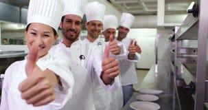 Cocineros sonrientes que se colocan en fila de donante de los pulgares para arriba almacen de video