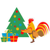 Cock decorates Christmas tree Stock Photo