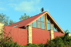 On the roof. Red rooster weathervane on the roof of the house, Russia Stock Photography