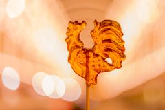Cockerel candy on a stick. Hard candy rooster. Rooster candy symbol Royalty Free Stock Image