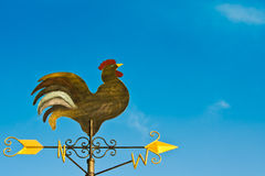 A cockerel wind vane. Against blue sky stock images