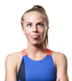 Cockeyed Blue eyed blond girl. With tail hair in sportswear with crossed arms showing tongue and front standing on white isolated background Stock Images