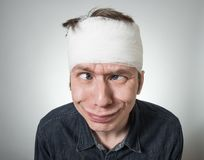 Man with bandage on his head. Cockeyed young guy with bandage on his head. Image related with treatment of the wounds Stock Photography